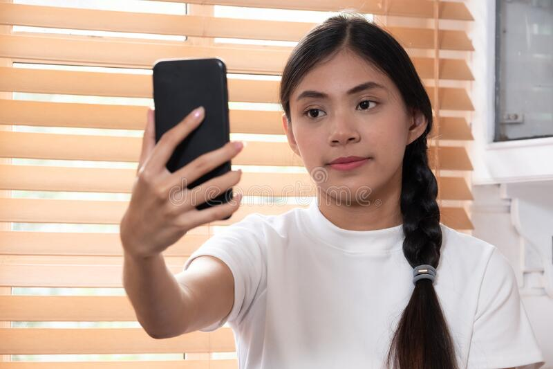 Young asian woman making video call on smartphone at home royalty free stock photography