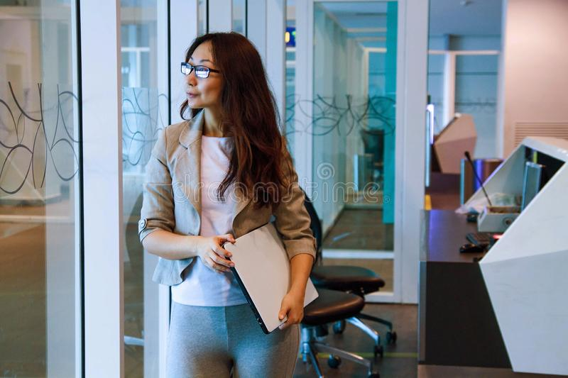 Young asian woman in office holding folder, smiling, portrait. Business concept royalty free stock photo