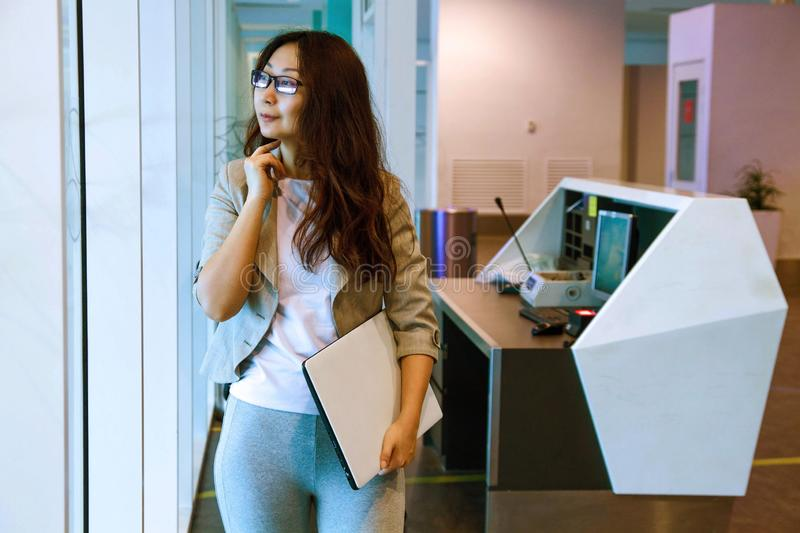 Young asian woman in office holding folder, smiling, portrait. Business concept stock photos