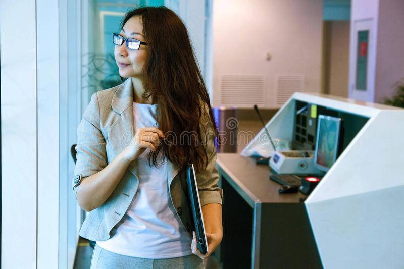 Young asian woman in office holding folder, smiling, portrait. Business concept stock photography