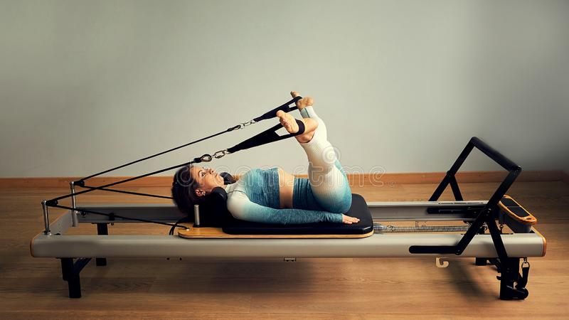 Young asian woman pilates stretching sport in reformer bed instructor girl in a studio stock photography