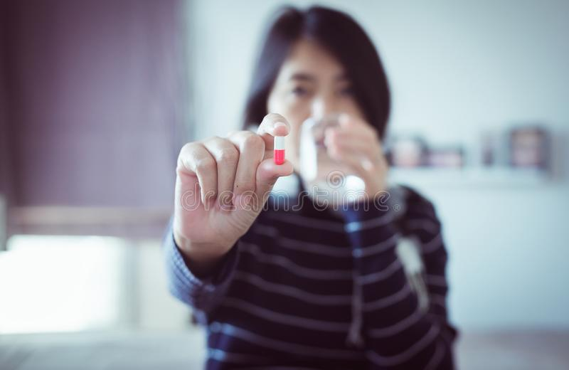 Young asian woman with pills or capsules on hand and a glass of water,Concept for health royalty free stock photo