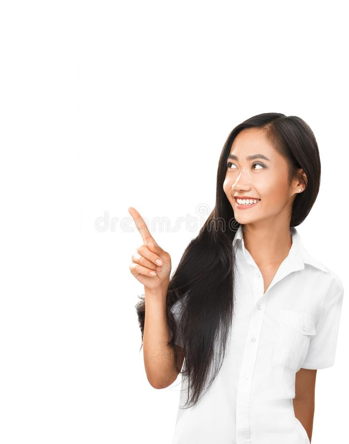 Young Asian woman pointing finger and looking in same direction. Photo for business projects, product presentation, interpersonal topics dating, flirting royalty free stock images