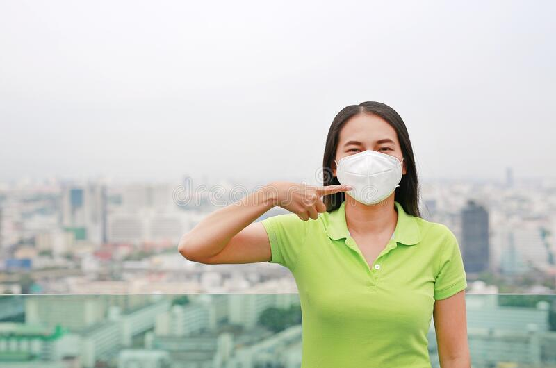 Young Asian woman pointing at wearing a protection mask against PM 2.5 air pollution in Bangkok city. Thailand. Reduce air stock photography