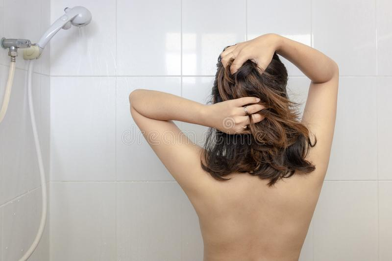 Young asian woman prepare to take a shower and wash hair under warm water falling from rain showerhead in white bathroom royalty free stock photo