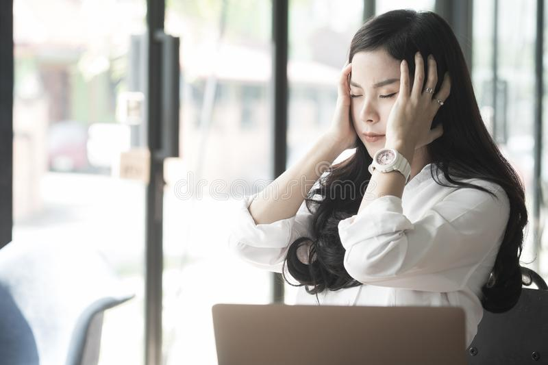 young asian woman put hand on head feeling tired at office. businesswoman frustrate and stress from hard work while sitting stock image