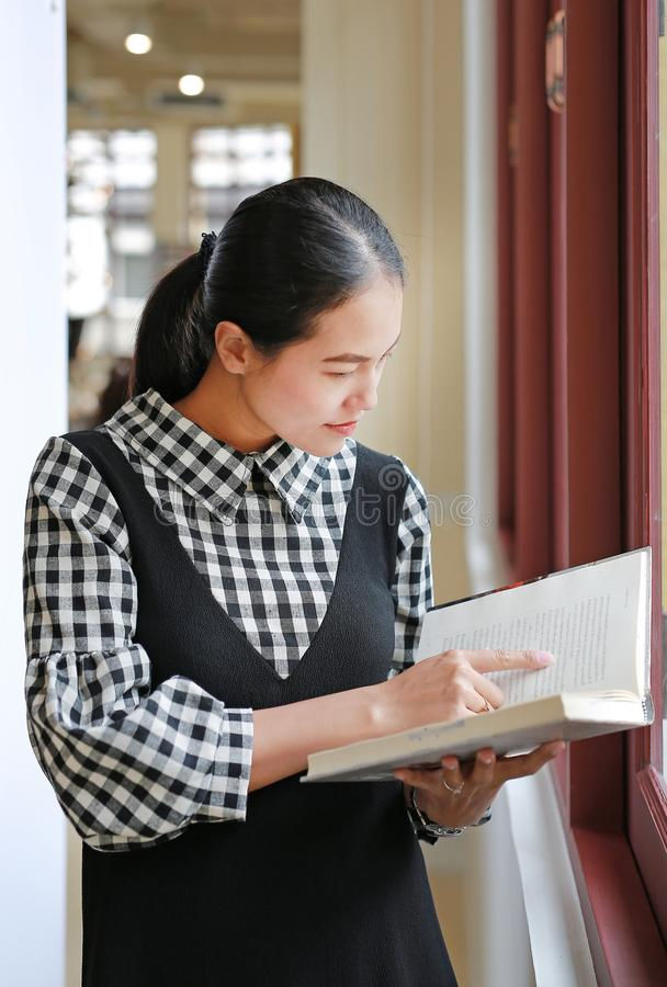 Young asian woman reading book in the library royalty free stock photography