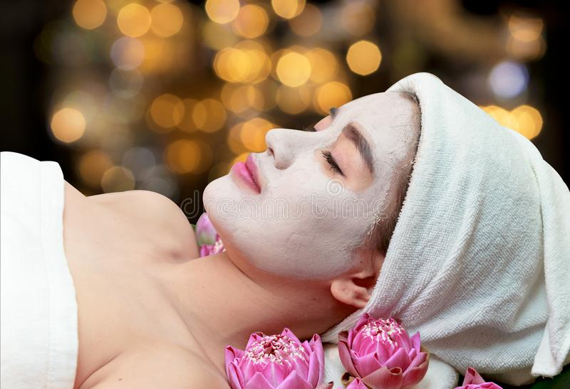 Asian woman receiving clay facial mask in spa beauty salon royalty free stock images
