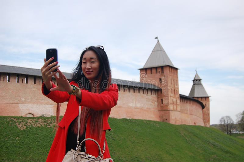 Young asian woman in red coat taking selfie by phone stock image
