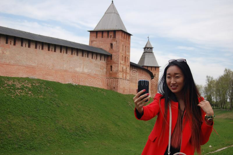 Young asian woman in red coat taking selfie by phone royalty free stock photos