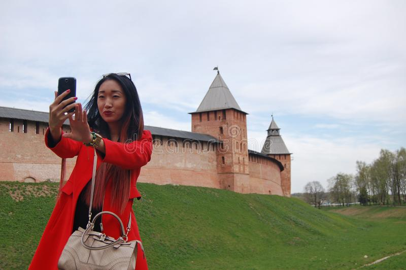 Young asian woman in red coat taking selfie by phone stock photo