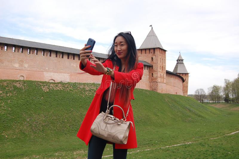 Young asian woman in red coat taking selfie by phone stock photography