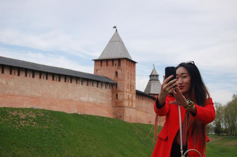 Young asian woman in red coat taking selfie by phone royalty free stock photo