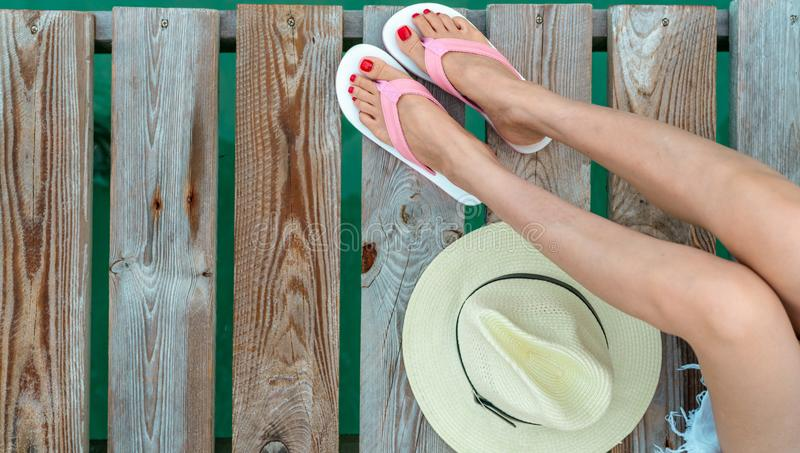 Young Asian woman with red pedicure wearing pink and white sandals sit on wooden bridge and put hat beside legs on holiday. Summer. Vacation. Summer vibes royalty free stock photos