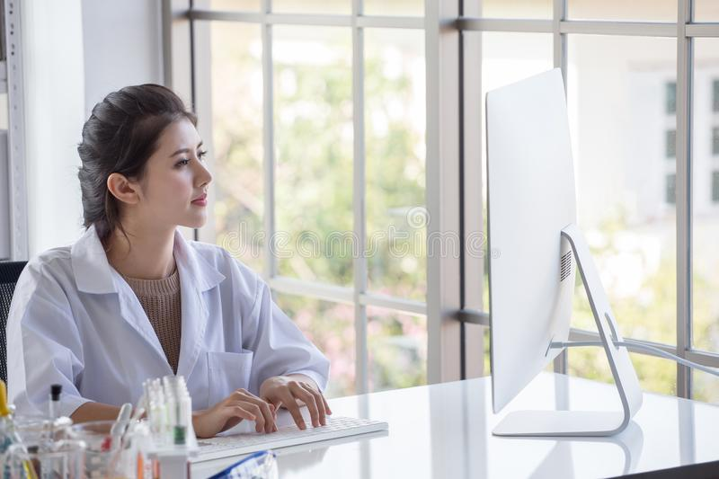 young  asian woman research scientist  preparing test tube and analyzing microscope With Computer in  Laboratory royalty free stock images