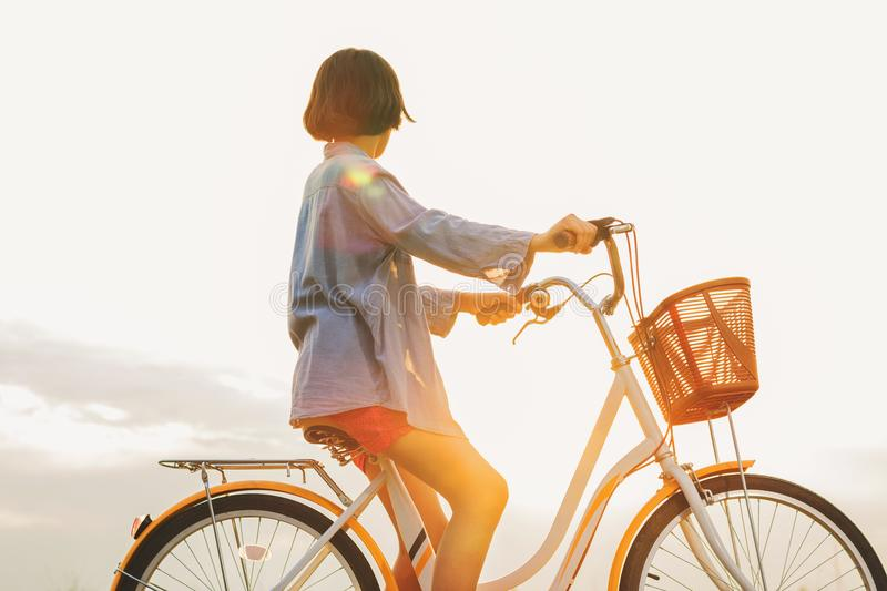 young asian woman riding bicycle at park royalty free stock photo