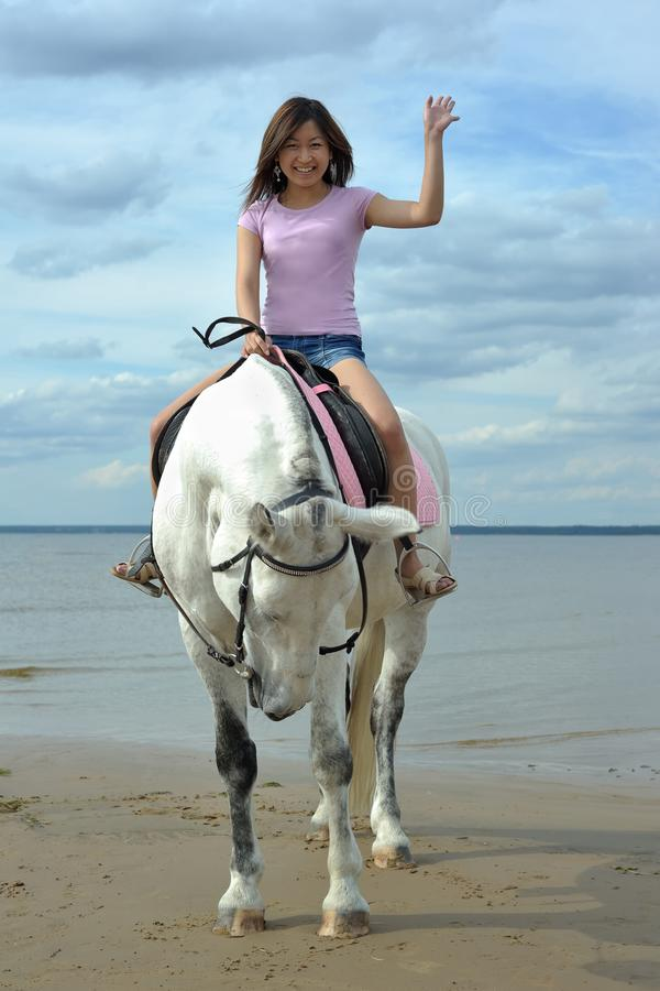 Young asian woman riding white horse stock photography