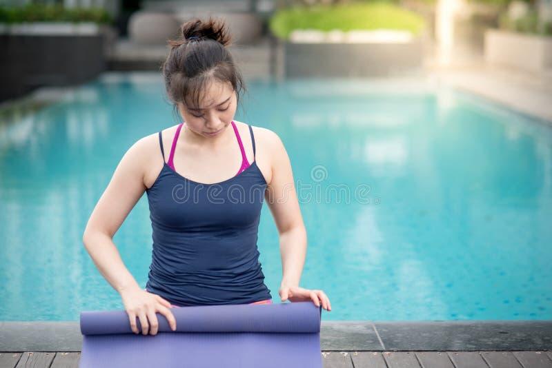 Young Asian woman rolling yoga mat near swimming pool stock photos