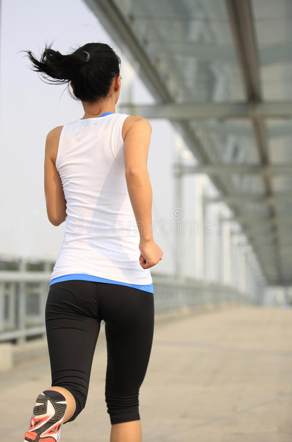 Young asian woman running at city footbridge royalty free stock photo