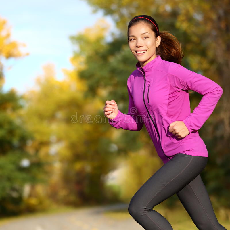 Young Asian woman running female jogger happy. Female runner jogging in park in autumn park forest in fall colors. Beautiful young sport model. Multi-ethnic royalty free stock photography