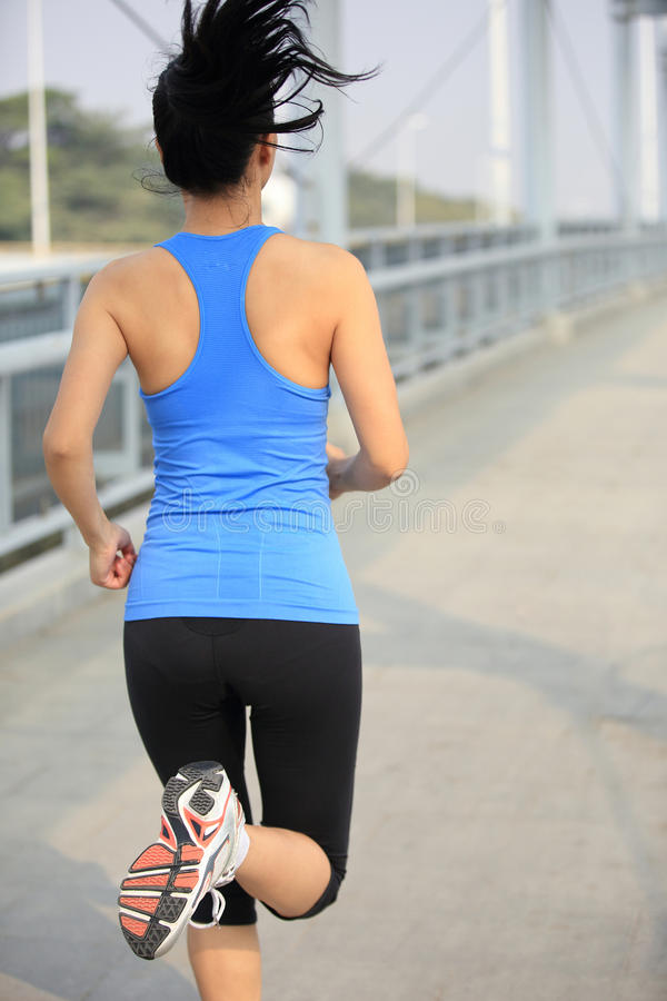 Young asian woman running at modern city footbridg. Beautiful healthy lifestyle young asian woman running at modern city footbridge stock photo