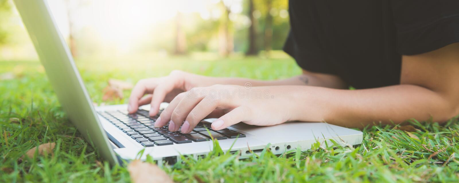 Young asian woman`s legs on the green grass with open laptop. Girl`s hands on keyboard. Distance learning concept. Happy hipster young asian woman working on royalty free stock images