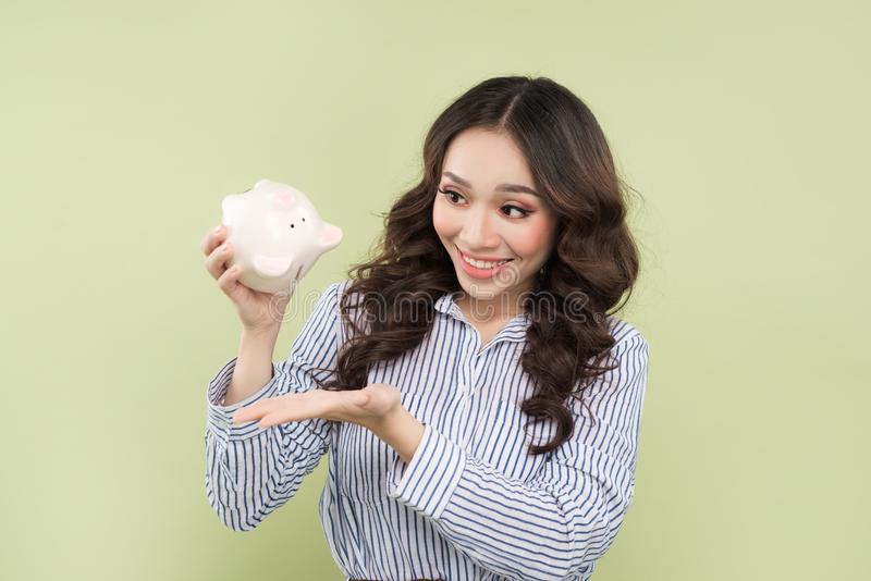 Young asian woman shaking out empty piggy bank on green background. stock image