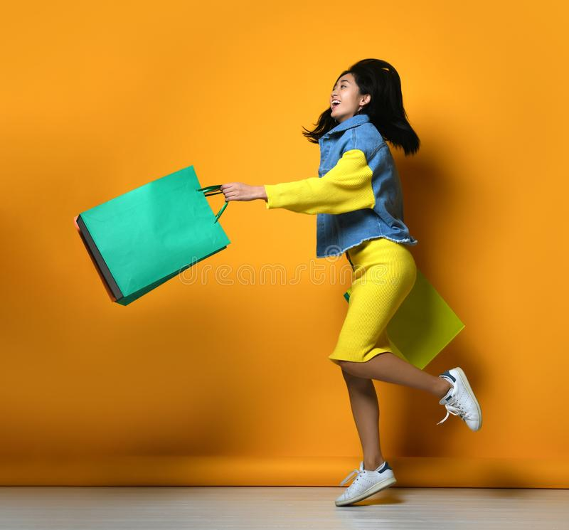 Young asian woman with shopping bags on color background stock photography