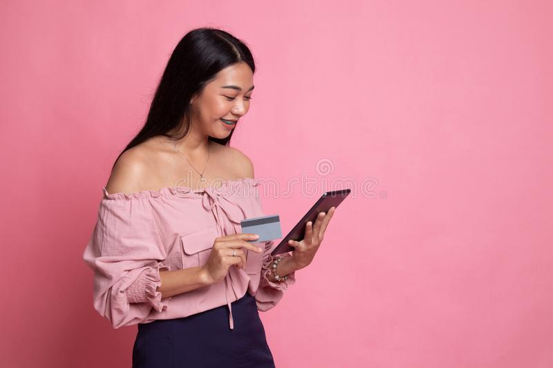 Young Asian woman is shopping online with credit card and tablet. On pink background royalty free stock image