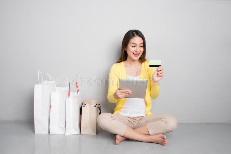 Young asian woman shopping online at home sitting besides row of. Shopping bags royalty free stock image
