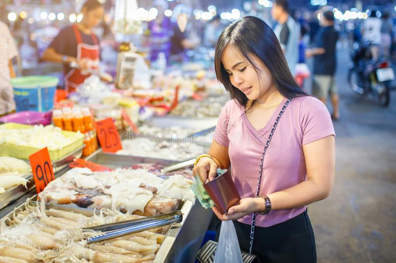 Young asian woman shopping for squid on ice in local market stall with fresh seafood royalty free stock image