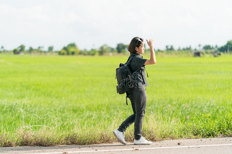 Woman with backpack hitchhiking along a road. Young asian woman short hair and wearing sunglasses with backpack hitchhiking along a road in countryside Thailand stock photos