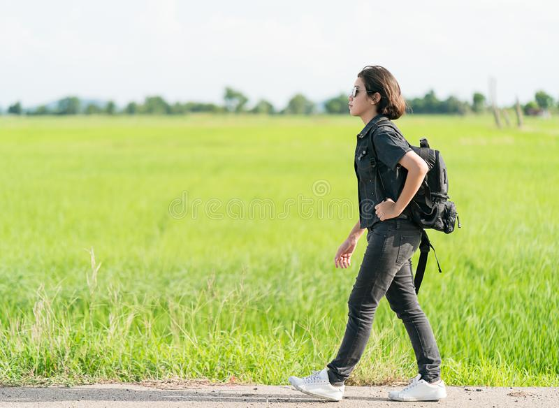 Woman with backpack hitchhiking along a road. Young asian woman short hair and wearing sunglasses with backpack hitchhiking along a road in countryside Thailand stock images