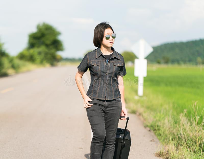 Woman with luggage hitchhiking along a road. Young asian woman short hair and wearing sunglasses with luggage hitchhiking along a road in countryside Thailand stock photos