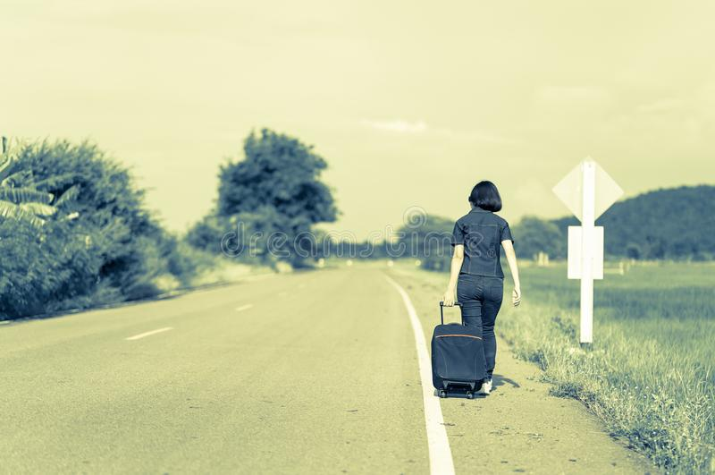 Woman with luggage hitchhiking along a road. Young asian woman short hair and wearing sunglasses with luggage hitchhiking along a road in countryside Thailand stock photography