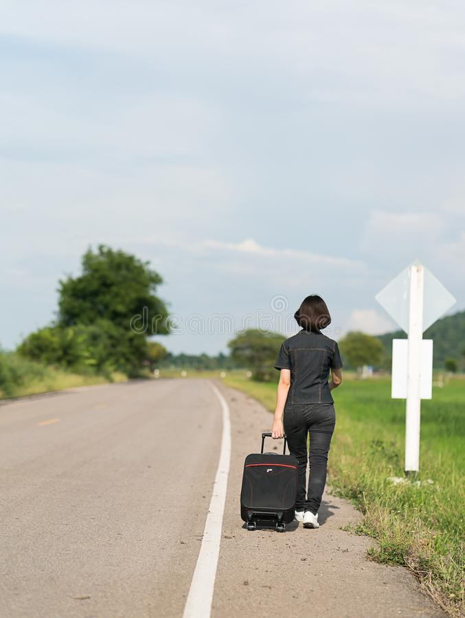 Woman with luggage hitchhiking along a road. Young asian woman short hair and wearing sunglasses with luggage hitchhiking along a road in countryside Thailand stock image