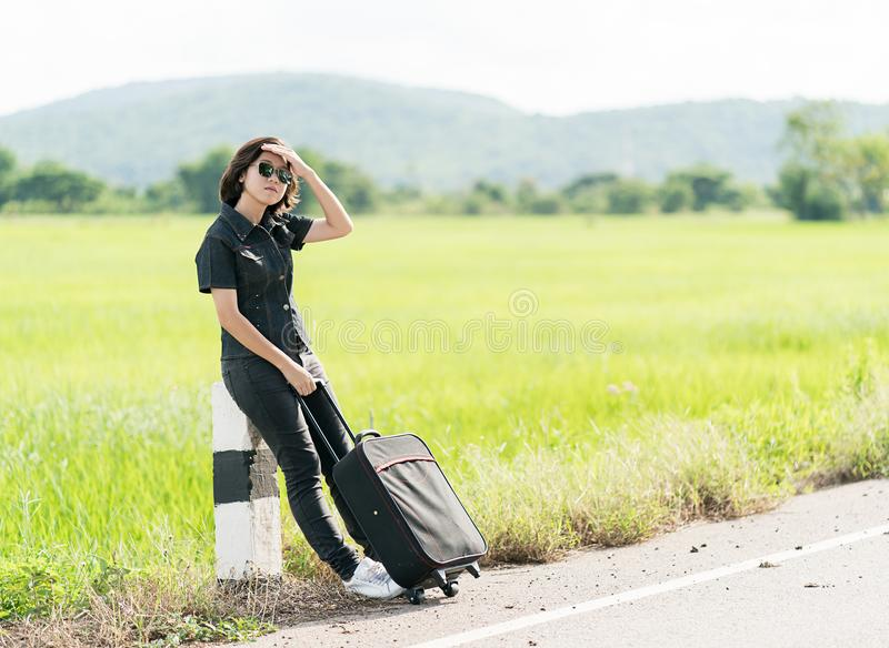 Woman with luggage hitchhiking along a road. Young asian woman short hair and wearing sunglasses with luggage hitchhiking along a road in countryside Thailand royalty free stock photography