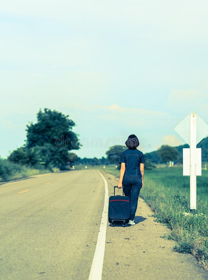 Woman with luggage hitchhiking along a road. Young asian woman short hair and wearing sunglasses with luggage hitchhiking along a road in countryside Thailand royalty free stock photo