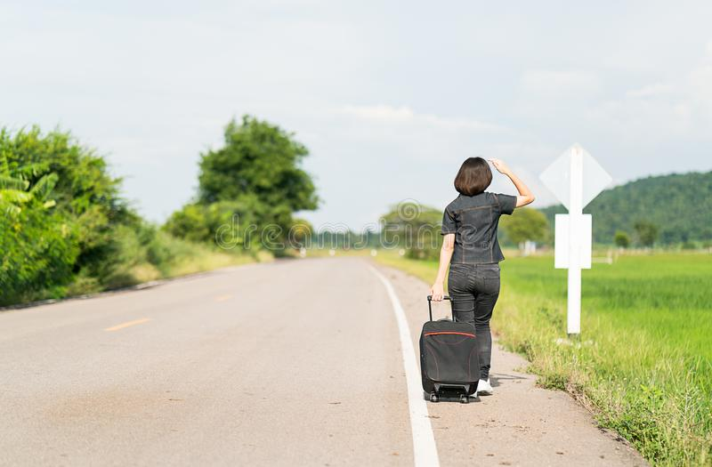 Woman with luggage hitchhiking along a road. Young asian woman short hair and wearing sunglasses with luggage hitchhiking along a road in countryside Thailand royalty free stock photos