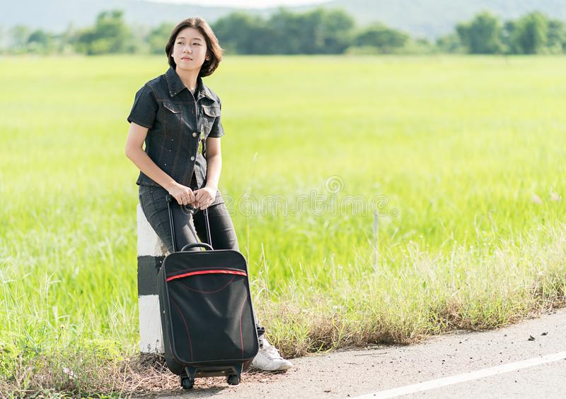 Woman with luggage hitchhiking along a road. Young asian woman short hair and wearing sunglasses with luggage hitchhiking along a road in countryside Thailand stock photo