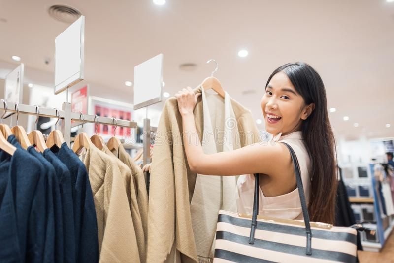 Young Asian Woman with Shoulder Bag Looking at Clothes Hanging o royalty free stock photography