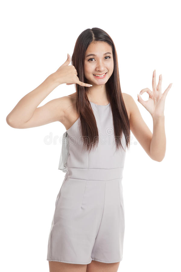 Young Asian woman show with phone gesture and OK sign stock photography