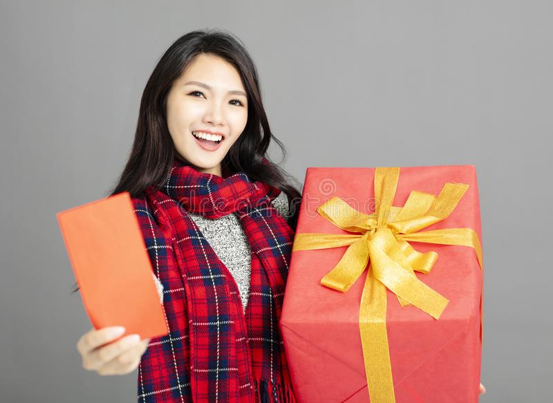 Asian woman showing red envelopes and gift for chinese new year. Young asian woman showing red envelopes and gift for chinese new year stock photo