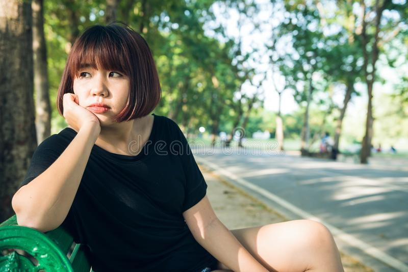 Young Asian woman sitting alone on the public bench in the park surrounded with nature and warm sunlight στοκ φωτογραφίες