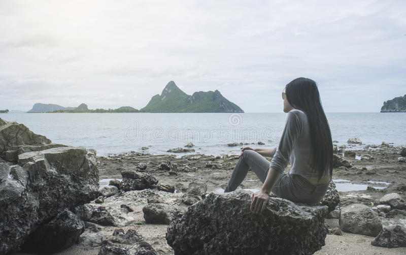 Young asian woman sitting on a rock near the sea,looked to the sea,chill out of summer,rest time,light effect added. Selective focus,filtered image royalty free stock photo
