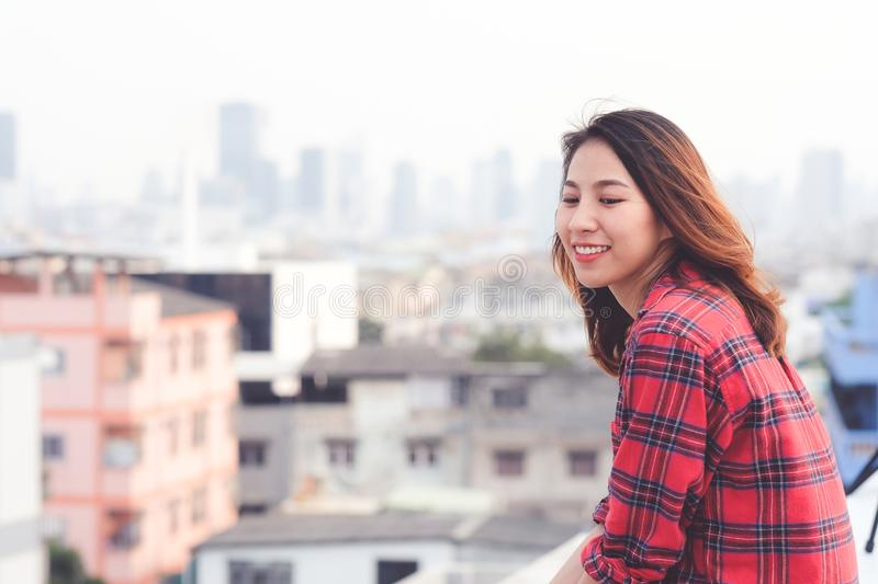Young asian woman sitting and smiling at rooftop outdoor in urba royalty free stock image