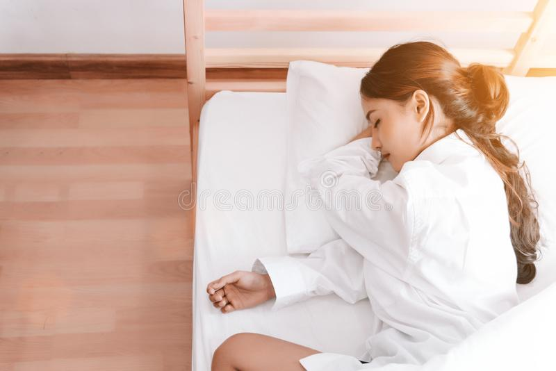 Young Asian woman sleeping on white bed in the morning. Beauty and Holiday concept. Vacation and Relax theme. Interior and People. Theme. Top view royalty free stock image