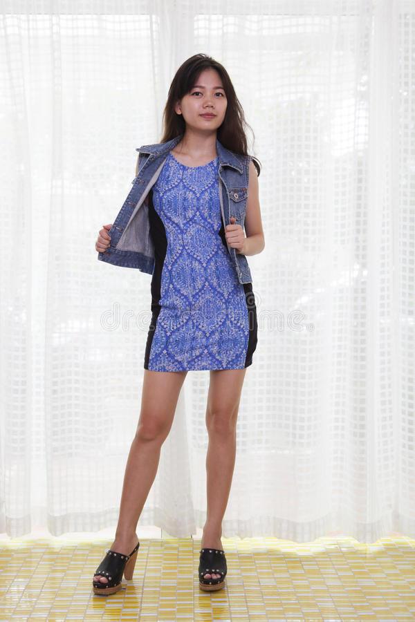 young asian woman with slim body standing with blue dress and jeans jacket shirt against with curtain stock images