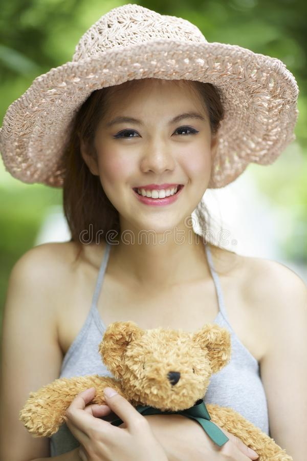Young asian woman smiling brightly and hug teddy bear at outdoor.  royalty free stock image