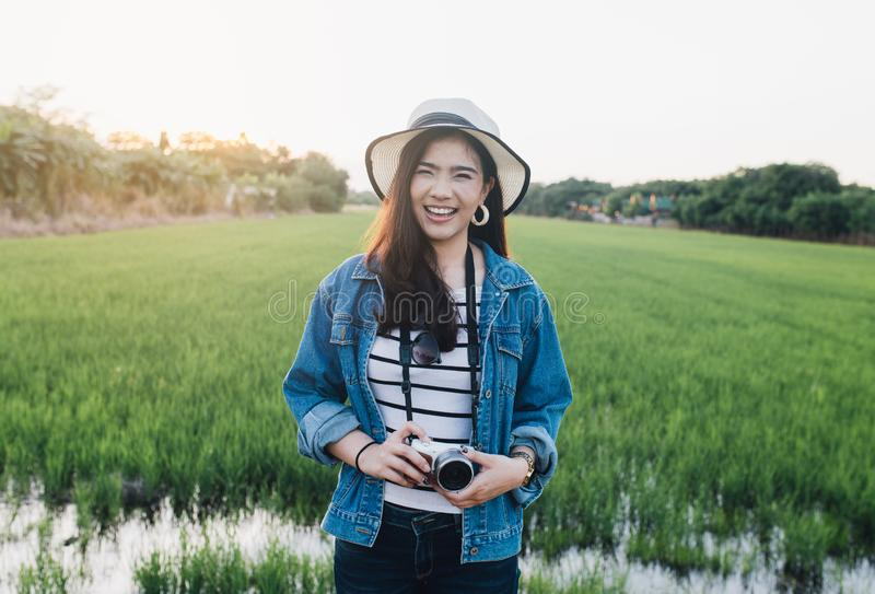 Young asian woman smiling in hat with camera. Girl enjoying at beautiful nature with sunset. Travel Summer Holiday Vacation stock photography